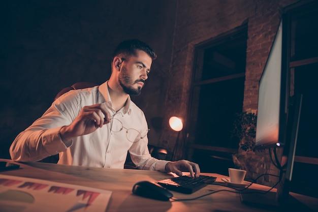 Серьезный задумчивый парень вычисляет печатный компьютер