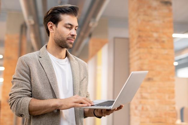 モダンなロフトオフィスに立っているベージュのジャケットで深刻な物思いにふけるハンサムな男性マネージャーとラップトップでデータを分析