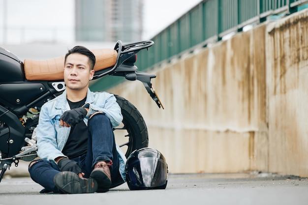 バイクの隣の地面に座って目をそらしている深刻な物思いにふけるハンサムなベトナム人男性
