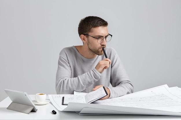 심각한 생각에 잠겨있는 남성 엔지니어가 손에 펜과 노트북을 유지하고 회의를 계획합니다.