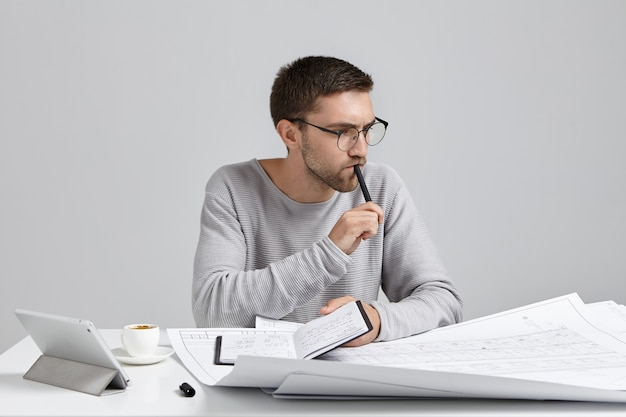 Serious pensive male engineer keeps pen and notebook in hands, plans meeting,