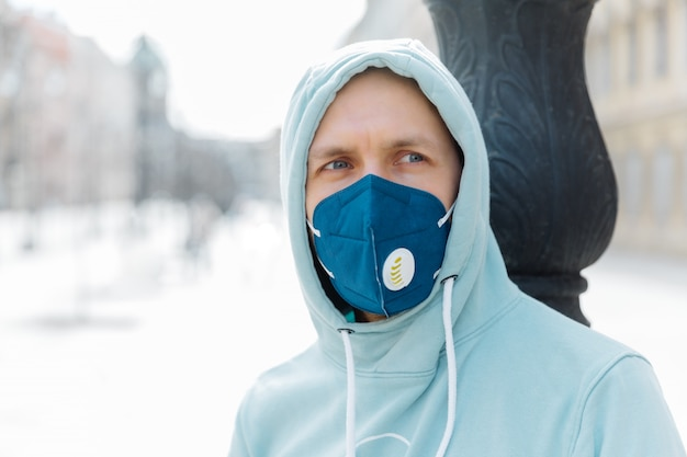 Serious pensive man wears hoodie and protective respiratory mask while walk on street, protects against infection with influenza virus or coronavirus, avoids public crowded places, cares about health