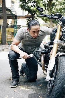 屋外でオートバイのエンジンを固定する手にレンチを備えた深刻な物思いにふけるメカニック