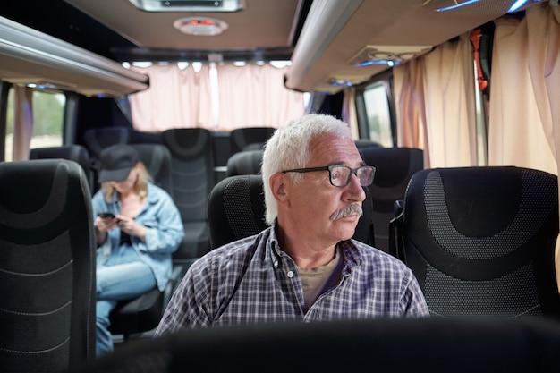 Серьезный задумчивый старший пассажир в очках сидит в современном автобусе и смотрит в окно