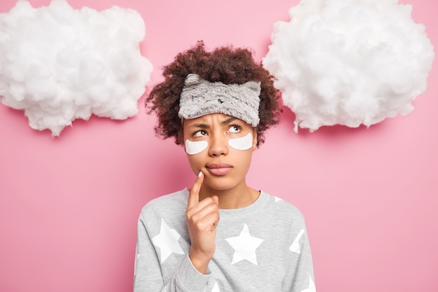 Serious pensive woman with curly afro hair tries to recall something in mind stands daydreaming keeps finger near mouth wears domestic clothes has lazy day at home