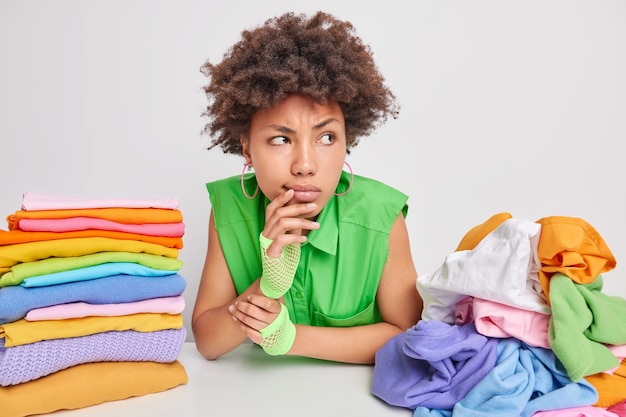Serious pensive young afro american woman focused away being deep in thoughts makes planning for weekends sits at table with piles of clothig folds laundry at home isolated over white