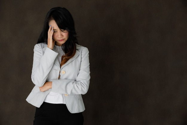 Serious pensive young asian businesswoman in classy outfit touching forehead and close eyes thoughtfully against dark gray background with empty space
