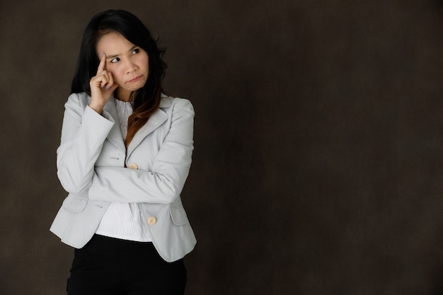 Serious pensive young asian businesswoman in classy outfit touching forehead and looking away thoughtfully against dark gray background with empty space