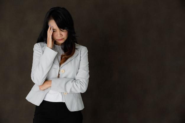 이마를 만지고 빈 공간이 있는 짙은 회색 배경에 대해 신중하게 눈을 감고 고상한 옷을 입은 진지한 생각에 잠겨있는 젊은 아시아 여성 사업가