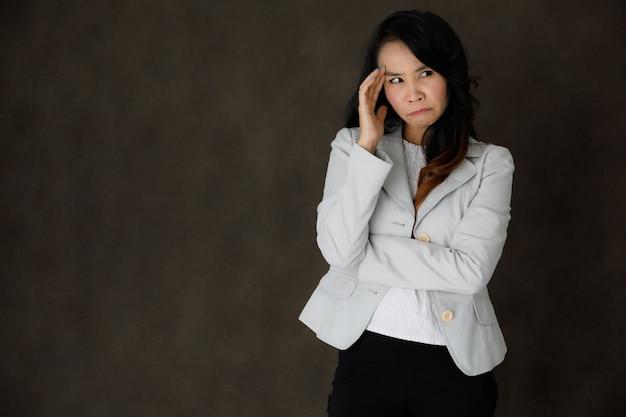이마를 만지고 빈 공간이 있는 짙은 회색 배경을 사려 깊게 바라보는 품위 있는 옷을 입은 진지한 생각에 잠겨있는 젊은 아시아 여성