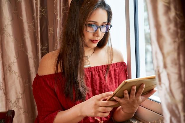 窓際に立っているときにデジタルタブレットでレポート、ニュース、記事を読んで深刻な物思いにふける若い女性
