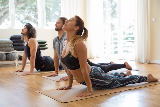 Serious people doing upward facing dog pose at class