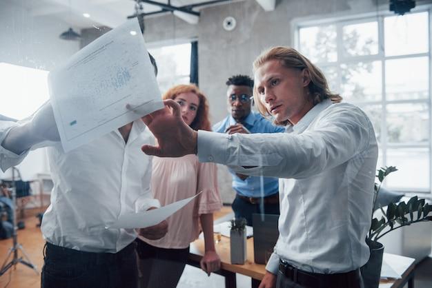 Серьезные люди. молодая многорасовая команда в официальной одежде в офисе, глядя на прайс-лист