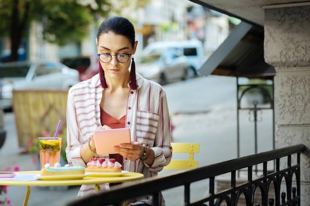 真面目な人。屋外のカフェに座っている間、現代のタブレットの画面を注意深く見ている穏やかな女性