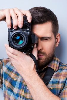 Serious photographer. portrait of confident young man in shirt holding camera in front of his face while standing against grey background