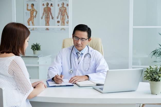 真面目な医師が患者の病歴をチェックし、彼女の苦情を聞き、診断を下す