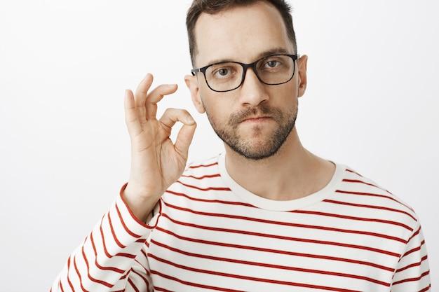Serio uomo arrabbiato incazzato con gli occhiali, bocca zippata con il gesto del dito e persona minacciosa di tacere o tacere