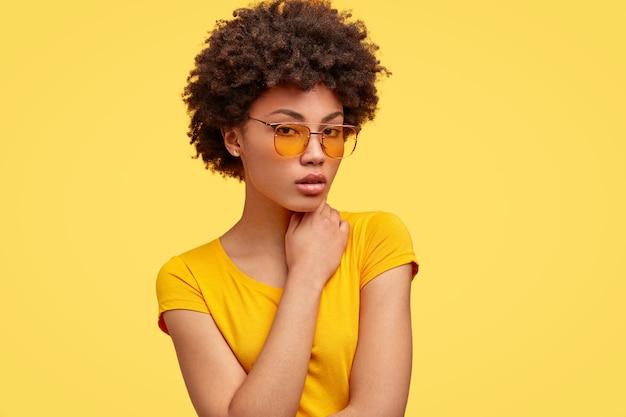 Hipster dall'aspetto piacevole serio con acconciatura afro