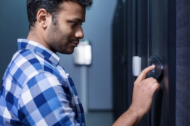 Serious pleasant young man looking at the control panel and pressing the button while entering the password