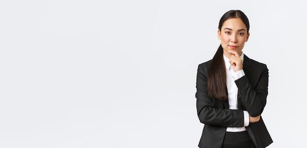 У серьезной довольной азиатской бизнес-леди есть интересная идея, она трогает подбородок и хитро смотрит в камеру, задумчиво стоит, думает, стоя в костюме на белом фоне