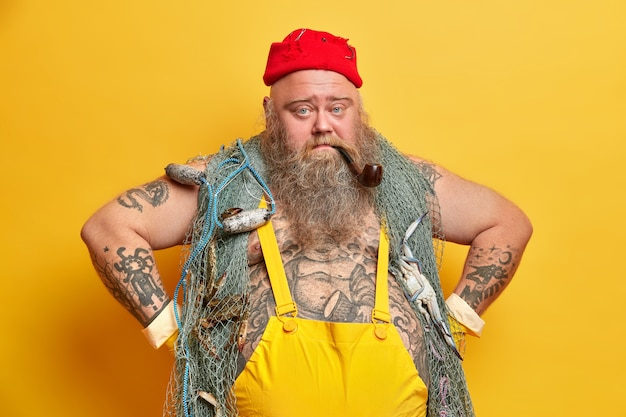 Serious plump tattooed man sailor stands in self confident pose keeps hands on waist smokes pipe wears overalls red hat with hooks carries fishing net