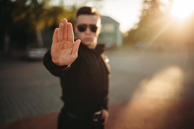 深刻な警察官が手の一時停止の標識を示しています