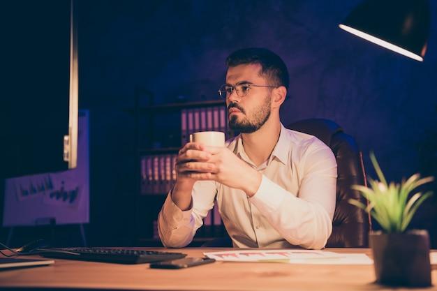 コーヒーの夜のオフィスを飲む深刻な熟考男