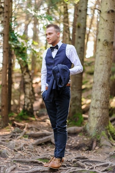 A serious portrait of a handsome groom in a blue suit and bow tie is standing against the backdrop of greenery in the forest.