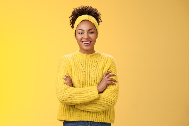 Serious powerful good-looking smiling african-american female femenist blogger cross hands chest confident pose grinning delighted enjoying watching working process, standing yellow background.
