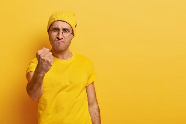 Серьезный влиятельный мужчина нуждается в уважении, поднимает кулак, недовольно смотрит, не позволяет, чтобы его оскорбляли, недовольно хмурится