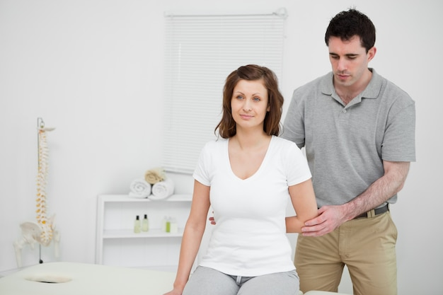Serious practitioner holding the elbow of a patient