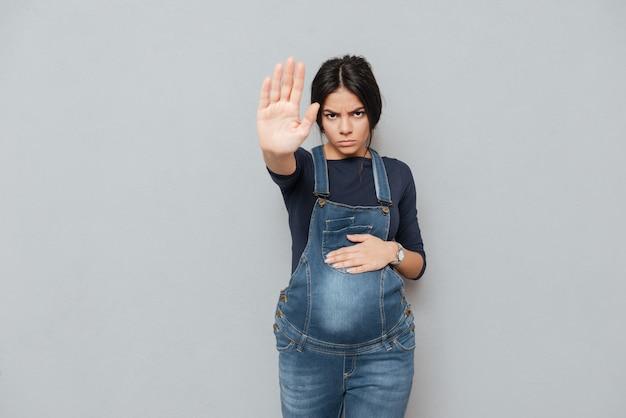 Серьезная беременная женщина делает жест остановки