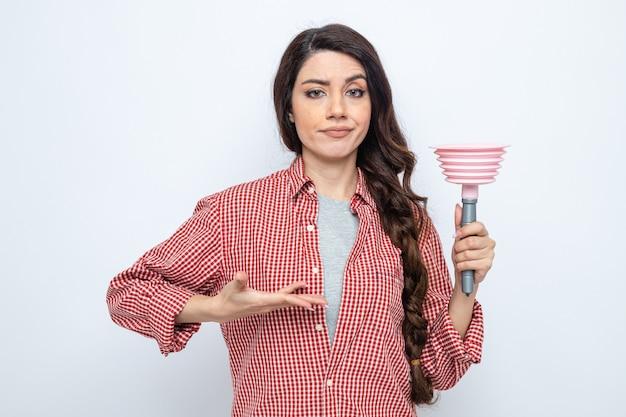 고무 플런저를 잡고 가리키는 심각한 백인 청소기 여성