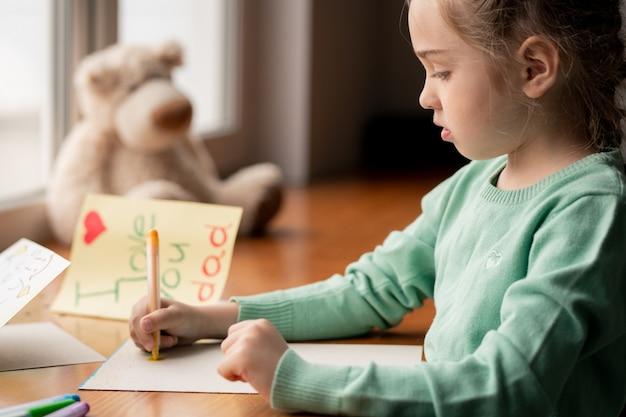 Серьезная красивая девушка в зеленом свитере сидит за столом и рисует фломастером картину для отца в своей комнате
