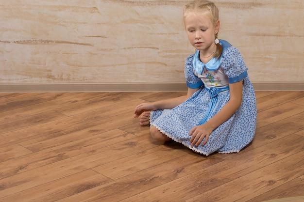 Серьезная красивая девушка на голубом платье, сидящем на коричневом деревянном полу.