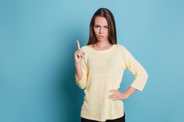 Серьезная красивая девушка указывает пальцем вверх и смотрит в камеру, изолированную на синем фоне