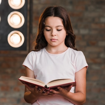Serious pretty girl reading book