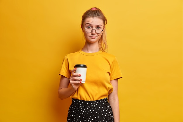 Serious pretty girl spends free time with new friend holds takeaway coffee drinks beverage and looks unhappily wears yellow t shirt optical glasses stands indoor