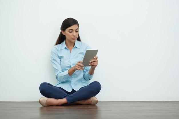 바닥에 태블릿에 노력하는 심각한 예쁜 여자