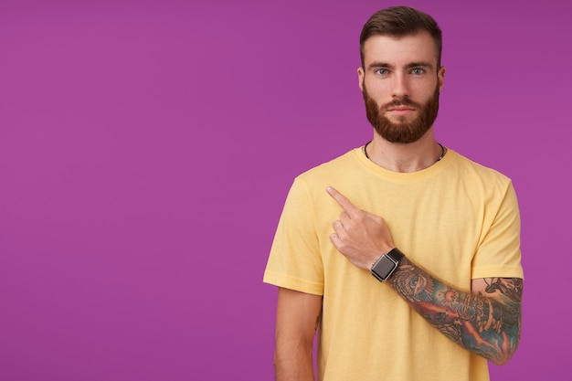 Serious pretty young tattooed unshaved man with trendy haircut pointing upwards with index finger with folded lips, standing on purple in casual clothes