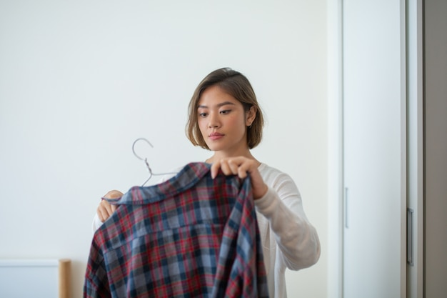 Serious pretty young woman hanging shirt on hanger at home