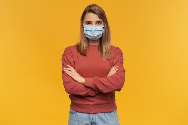무기와 코로나 바이러스에 대한 얼굴에 바이러스 보호 마스크에 심각한 예쁜 젊은 여자가 노란색 벽 위에 고립 된 교차
