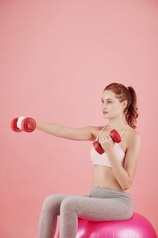 Серьезная симпатичная молодая женщина сидит на розовом фитнес-мяче и делает упражнения с гантелями