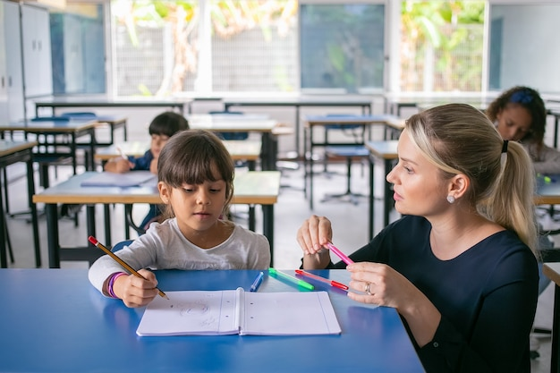 Serious primary school teacher helping girl to cope with her task