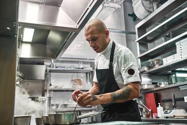 Серьезный профессиональный повар в фартуке с несколькими татуировками на руках готовит на кухне ресторана