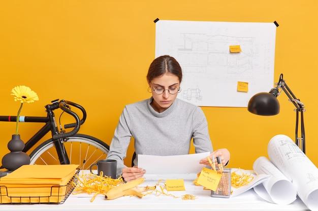 스케치와 청사진으로 dekstop에서 종이 포즈에 집중된 진지한 전문 여성 건축가가 새로운 프로젝트를 개발합니다.