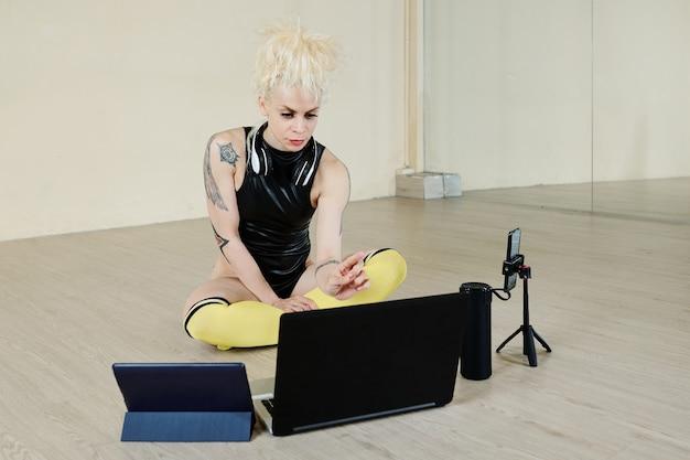 고객을위한 온라인 댄스 레슨을 주최하기 위해 컴퓨터, 스마트 폰 및 태블릿을 설정하는 심각한 전문 여성 댄서