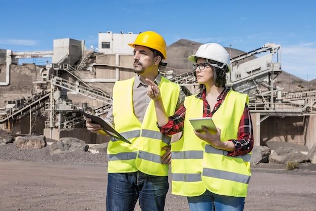 태블릿이 산업 건설 현장을 방문하는 동안 엔지니어링 개체에 대한 클립 보드가있는 남성 엔지니어의 의견을 묻는 심각한 전문 여성 관리자
