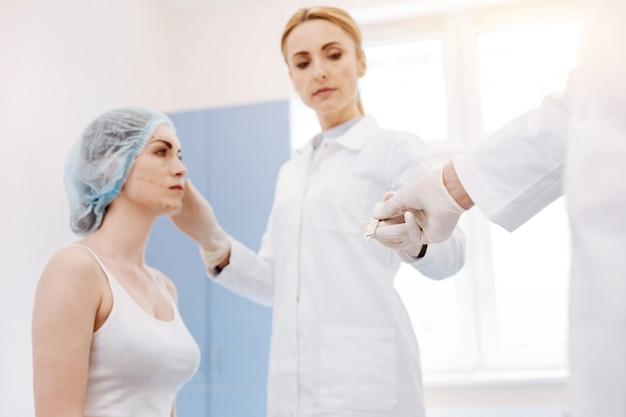 真面目なプロの女性外科医が患者の前に立ち、美容整形手術中にメスを取ります
