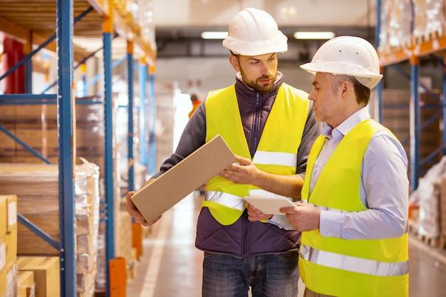 Серьезные профессиональные мужчины, работающие вместе при подготовке товаров к отправке